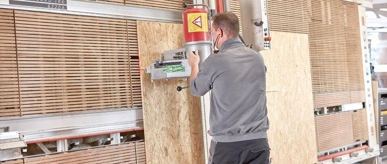 Situativ: Mitarbeiter schneidet Holz mit Maschine